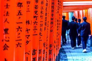 portes torii rouges dans le sanctuaire fushimi inari avec des hordes d'élèves japonais à kyoto au japon photo