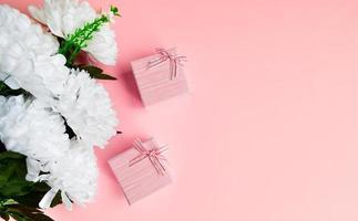 deux coffrets roses avec un bouquet de fleurs blanches. photo