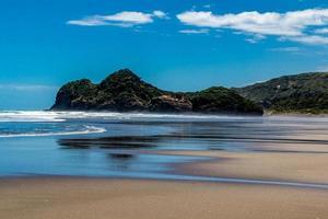 plages de sable, falaises et eaux ondulantes sur la plage de Bethels. Auckland, Nouvelle-Zélande photo