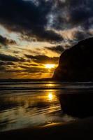 coucher de soleil et vagues se précipitant sur la plage. plage de bethels, auckland, nouvelle-zélande photo