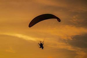 la silhouette du paramoteur au coucher du soleil photo