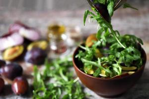salade saine mélanger les mains des hommes avec une cuillère et une fourchette. salade de prunes de roquette. photo