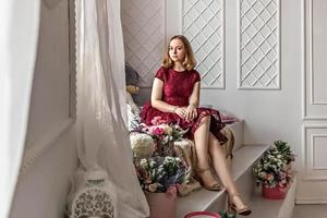 une jolie jeune fille élégante vêtue d'une élégante robe bordeaux est assise près de la fenêtre de sa chambre. adolescent. remise des diplômes à l'école, au collège photo