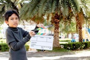 garçon asiatique tenant un panneau de couleurs d'ardoise de film pour l'industrie du cinéma et de la télévision photo