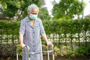 Une vieille dame asiatique âgée ou âgée marche avec un marcheur et porte un masque facial pour protéger l'infection de sécurité et tuer le nouveau virus du coronavirus covid-19. photo