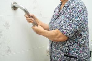 Une patiente asiatique âgée ou âgée utilise une passerelle en pente pour gérer la sécurité avec un assistant de soutien dans la salle d'hôpital de soins infirmiers concept médical solide et sain. photo