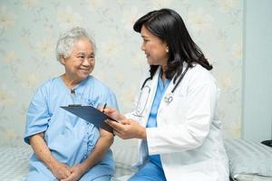 un médecin parle de diagnostic et note sur le presse-papiers avec une vieille dame asiatique âgée ou âgée allongée sur son lit dans une salle d'hôpital de soins infirmiers photo