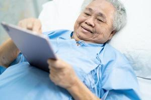 patiente asiatique âgée ou âgée tenant dans ses mains une tablette numérique et lisant des e-mails tout en étant assise sur son lit dans une salle d'hôpital de soins infirmiers, concept médical solide et sain photo