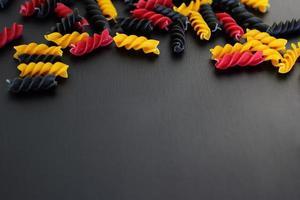 pâtes, repas italien en spirale de couleur végétarienne crue, fond noir, espace de copie, vue de dessus photo