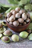 noix dans un bol. feuilles de noix noix dans une peau verte photo
