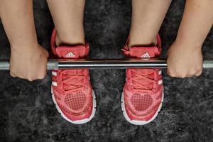 jambes d'une fille en baskets au bar de la salle de sport. mode de vie sain, sport. photo