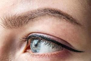 oeil féminin de couleur bleue d'un gros plan de jeune fille. maquillage des yeux et des sourcils.maquillage permanent pour les paupières et les sourcils photo