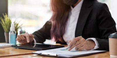 femme d'affaires en gros plan à l'aide d'une calculatrice et d'un ordinateur portable pour faire des finances mathématiques sur un bureau en bois dans un bureau et des antécédents de travail, fiscalité, comptabilité, statistiques et concept de recherche analytique photo