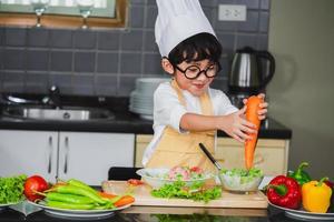 garçon asiatique, fils, cuisine, salade, nourriture, tenir, cuillère bois, à, légume, tenue, tomates, et, carottes, poivrons, sur, assiette photo