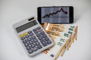 Billets de 50 euros avec calculatrice et graphique sur fond blanc photo
