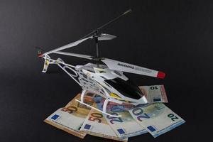 Hélicoptère modèle au-dessus de billets en euros de différentes dénominations photo