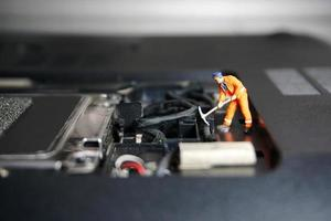 figure de travailleur technicien debout sur une vieille clé USB. il prend en charge le concept. photo