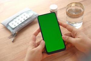 gros plan de la main des femmes utilisant un téléphone intelligent et des pilules médicales sur la table photo