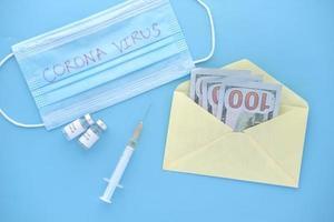 vaccin contre le coronavirus, seringue et espèces en dollars américains sur fond bleu photo