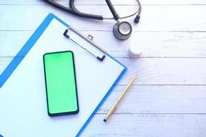 composition plate du téléphone intelligent avec écran vide sur la table de la clinique photo