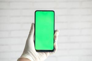 main dans des gants en latex tenant un téléphone intelligent avec écran vert photo