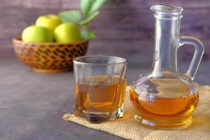 vinaigre de pomme en bouteille de verre avec pomme verte fraîche sur table photo