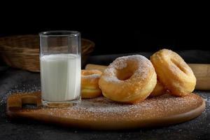 beignets avec du sucre sur une plaque en bois sur un fond de table sombre photo