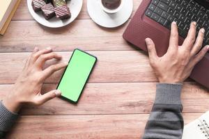 vue de dessus de la main de l'homme à l'aide d'un téléphone intelligent et en tapant sur un ordinateur portable photo