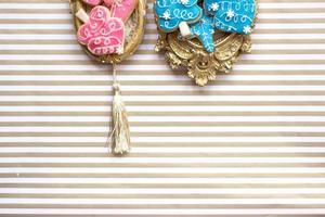 gros plan de biscuits de noël ou d'hiver roses faits maison servis sur un cadre photo ou un sentier doré vintage, espace pour copie
