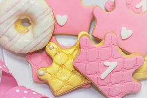 biscuits au glaçage royal du premier anniversaire - biscuits en forme de couronne rose et doré avec le numéro 1 photo