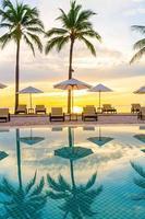 Parapluie et chaise autour de la piscine de l'hôtel resort avec lever de soleil le matin photo