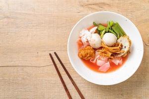nouilles de style thaï avec assortiment de tofu et boule de poisson dans une soupe rouge photo