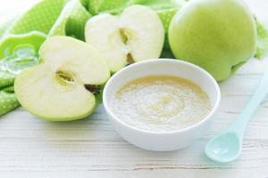 bol avec de la nourriture pour bébé aux fruits et des pommes photo