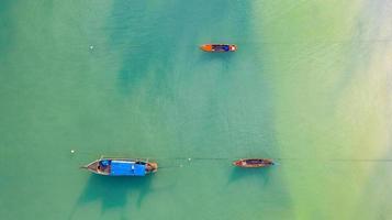 vue aérienne de dessus, bateau de pêche, bateau touristique flottant sur une mer claire et peu profonde, belle eau bleu vif dans l'océan photo