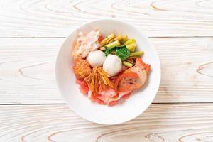 nouilles sèches de style thaï avec assortiment de tofu et boule de poisson dans une soupe rouge photo