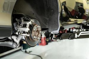 voiture à disque close up - mécanicien dévissant des pièces automobiles tout en travaillant sous une voiture soulevée photo