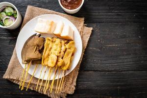 satay de porc avec votre sauce aux cacahuètes et cornichons qui sont des tranches de concombre et des oignons au vinaigre photo