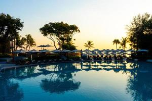 Parapluie et chaise canapé autour de la piscine extérieure de l'hôtel resort pour les vacances de voyage photo