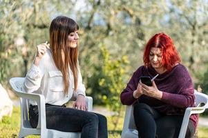 amies utilisant un smartphone et fumant une cigarette photo