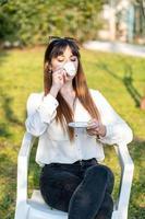 fille buvant du café dans le jardin photo