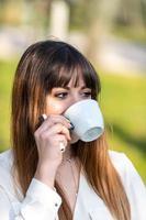 fille buvant une tasse de thé dans le jardin photo