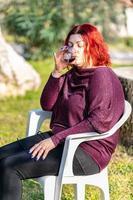 fille boit un gobelet de vin rouge dans le jardin photo