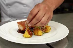 chef décorant un repas péruvien traditionnel, chicharron de panceta de cerdo photo