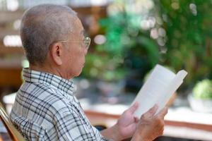 senior asiatique retraité assis sur un banc et lisant un livre à la maison arrière-cour pendant le temps libre photo