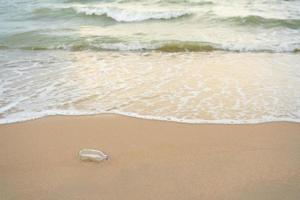 une bouteille en verre vide a été jetée sur la plage photo