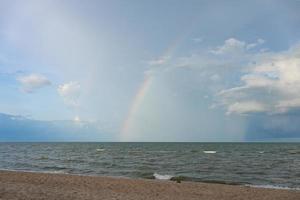 arc-en-ciel au-dessus de l'océan après l'arrêt de la pluie photo