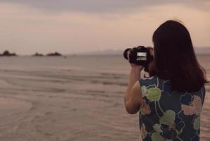 portrait de jeune femme utilisant un appareil photo pour prendre une photo de la plage pendant les vacances d'été