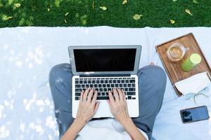 personne travaillant sur un ordinateur portable à l'extérieur photo