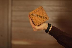 une plaque en bois a un mot réservé. la main masculine tient une plaque en bois avec l'inscription réservée isolée sur fond blanc. mise au point sélective. photo