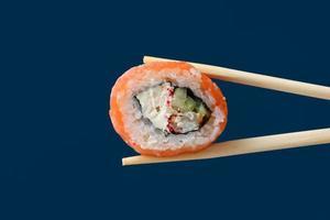 gros plan sur un rouleau de sushi au saumon frais avec des baguettes en bois photo
